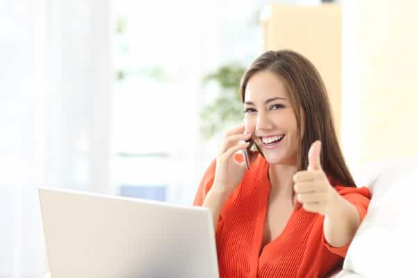 Hypnothérapeute au téléphone à un client, avec son pouce vers le haut, souriant.