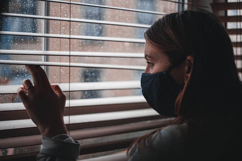 Femme au masque, en lock-out, regardant tristement à travers une fenêtre pluvieuse sur le monde extérieur